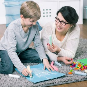 51793824 - young woman and boy drawing a picture during home lesson