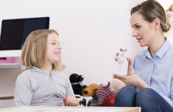 80159898 - child counselor discussing drawing with smiling girl during play therapy